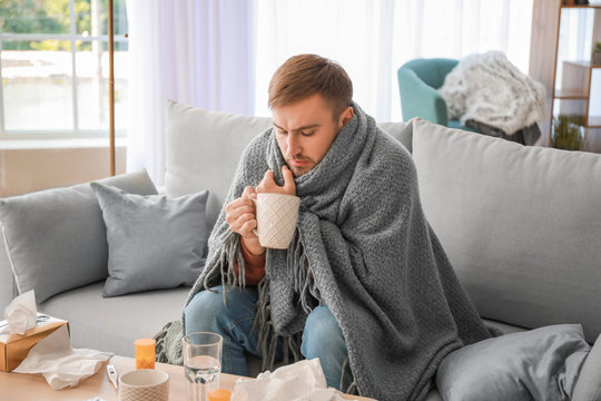 Sick man drinking hot tea at home