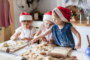 Kids cooking Christmas gingerbread cookies in cozy home kitchen. Funny children chefs in santa hats prepare holiday food. Cute girls make homemade cake. Lifestyle authentic moment. Family traditions.