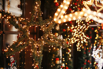 Stylish christmas star illuminated and fir branches with red and gold baubles, golden lights bokeh on front of building at holiday market in city street.Christmas street decor