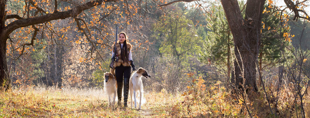 Portrait of a beautiful girl hunter with dogs
