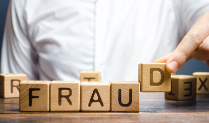 Wooden blocks with the word Fraud and man. Cheating white-collar . The crime. Theft of another's property. Anti-corruption in the financial sector. Deception and abuse of trust.