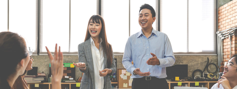 Banner of asian woman introduce about herself with new friend or new colleague at creative meeting room office. Confident female present work or project with opinion from colleague.