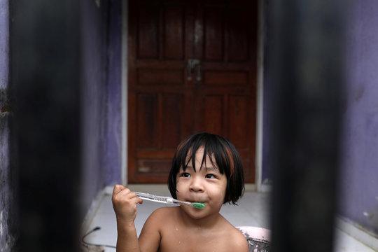 A girl brushes her teeth in Mawlamyine