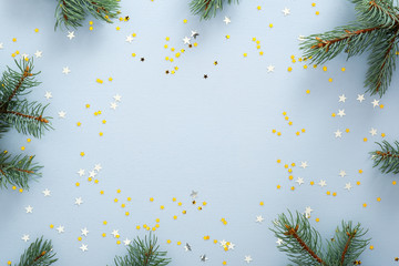 Blue Christmas background with fir tree branches and glitter confetti stars. Christmas, New Year, winter holidays concept. Xmas frame, banner mockup.