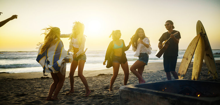 multiethnic group of californians dancing around fire pit on beach