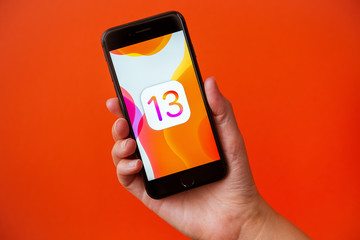 Kyiv, Ukraine - September 19, 2019: Studio shot of hand holding Apple iPhone 8 with an abstract wallpaper image about the release of the new iOS 13 version that Apple Inc. released today