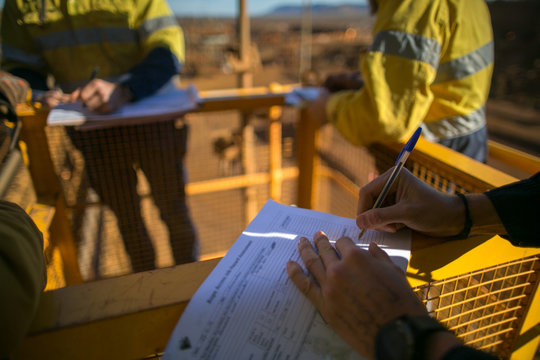 Rope access miner supervisor sigh of JSA risk assessment permit to work on site prior to performing high risk work on construction mine site, Perth, Australia