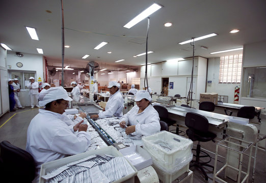 Employees work on condoms in a factory in Buenos Aires