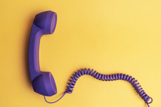 purple telephone receiver on yellow background