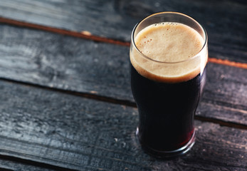 Obraz A glass of dark craft beer porter on a wooden table in a pub with copyspace - fototapety do salonu