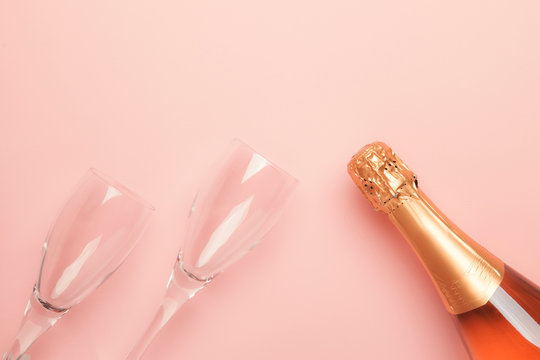 Bottle with pink sparkling wine or rose champagne and glasses, trendy pink background with place for text, holiday or date concept, flat lay, top view