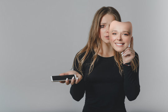 Portrait of a sad girl with a smartphone in one hand and a smiling mask in the other hand.