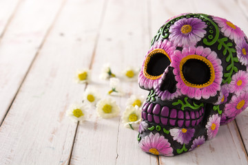 Typical Mexican skull with flowers painted on wooden table. Dia de los muertos. Copy space