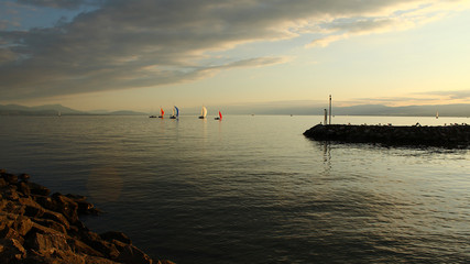 Beautiful sunset at the Lake Geneva in Lausanne, Switzerland, with colorful sailboats in the distance