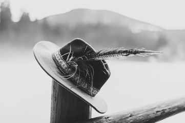 Hat with feathers handmade  on a wooden fence, a column in the winter on the background of the mountains. Close up. Black and white photo.