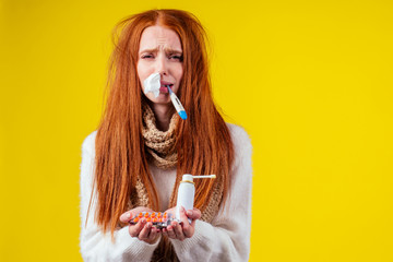 unwell redhaired ginger woman runny nose wearing knitted sweater and scarf with many pills in hand in studio yellow background