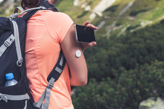 Active life of diabetics, woman hiking and checking glucose level with a remote sensor and mobile phone, sensor checkup glucose levels without blood