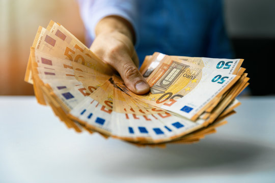 consumer loan or prize money concept - hand with euro banknotes