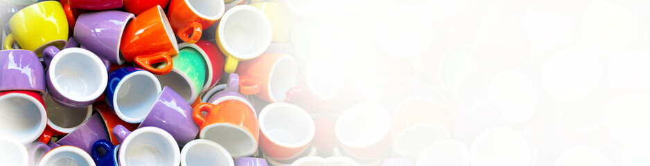 Heap of colorful cups for espresso coffee - concept of coffee addiction and crockery products. Wide panoramic image, Half banner format. Fade foggy horizontal banner.