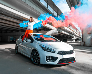 Confident and beautiful young woman in casual sports wear sitting on new car and rejoycing.