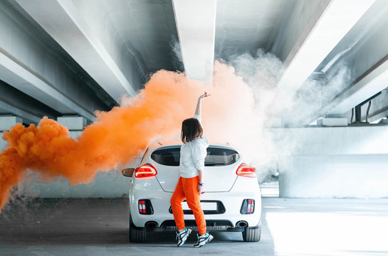 Confident and beautiful young woman in casual sports wear dancing near new car and rejoycing.