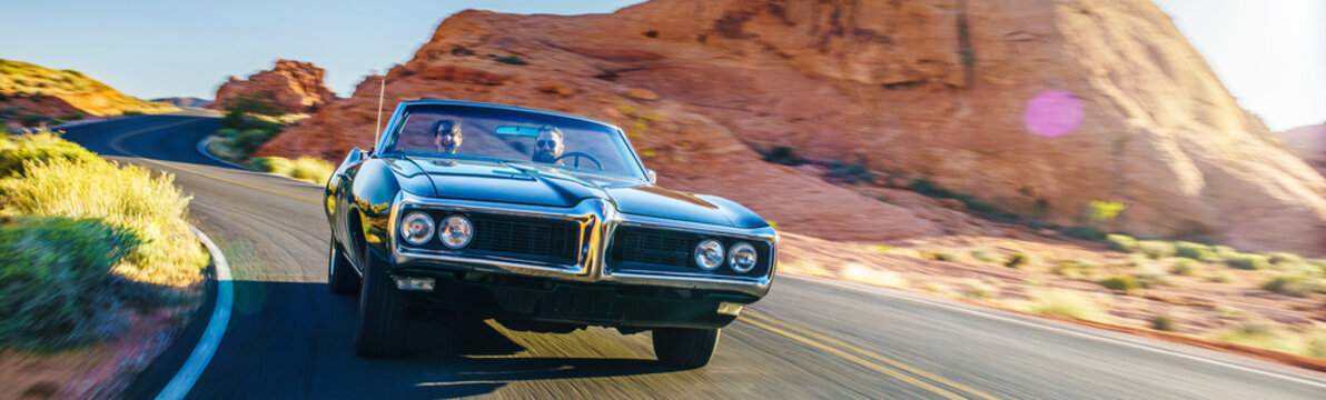 couple driving together in cool vintage car through desert