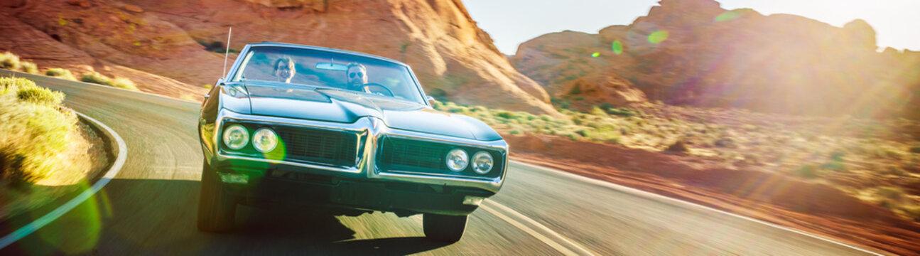 driving fast through desert in vintage hot rod car