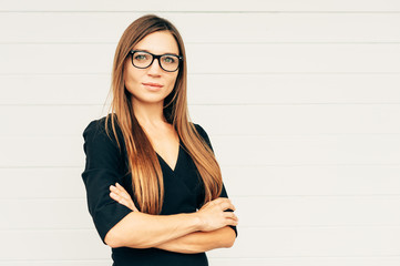 Close up portrait of beautiful young businesswoman wearing eyeglasses, arms crossed
