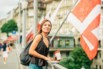 Outdoor portrait of beautiful young woman in the city, wearing backpack, holding cup of take away coffee. Image taken in Lausanne downtown, place Bel Air, Switzerland