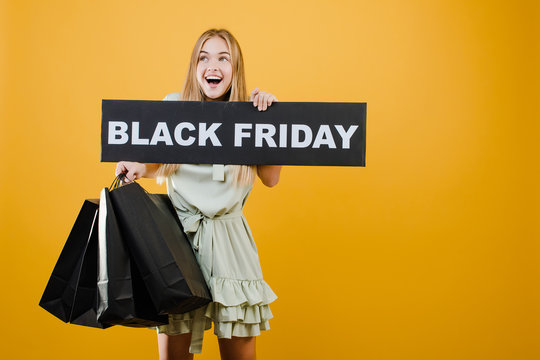smiling happy beautiful woman has black friday sign with paper shopping bags isolated over yellow