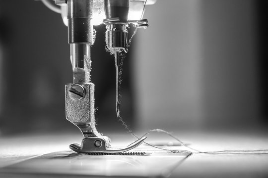 Close-up needle of white industrial sewing machine use sew cloth with black and white tone (monochrome).