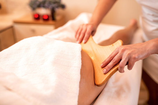 Masseuse holding a hand held wooden massage tool