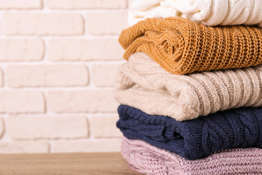 Bunch of knitted pastel color sweaters with different knitting patterns perfectly folded in stack on brown wooden table, white brick wall background. Fall winter season knitwear. Close up, copy space.