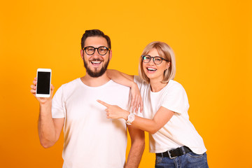 Young beautiful hipster couple having fun posing over isolated yellow background. Portrait of tall man with groomed beard and his short attractive blonde girlfriend. Copy space, close up.