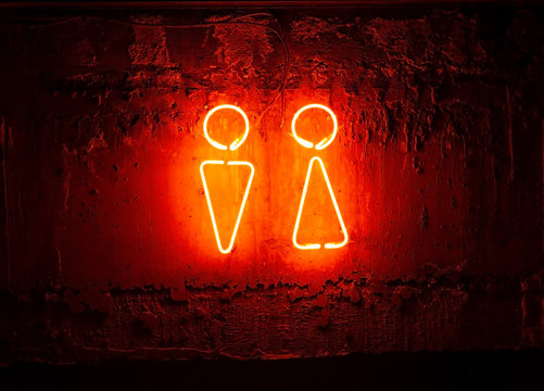 Neon toilet sign. Sign of man and woman on the wall.