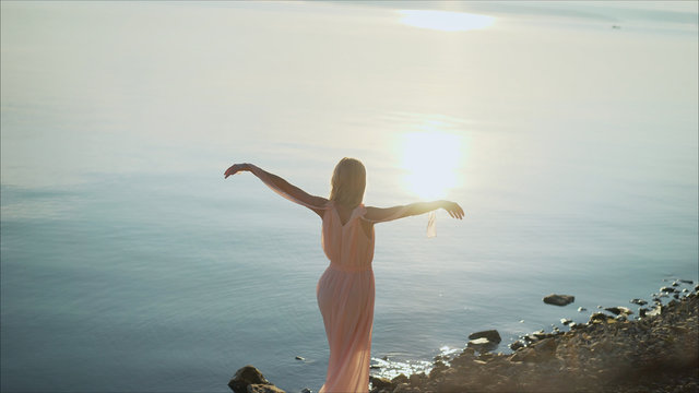 Beautiful young woman standing in sea with waves on sandy beach against orange sky at sunset. Summer travel. A young girl is standing against the sunset in a summer dress.