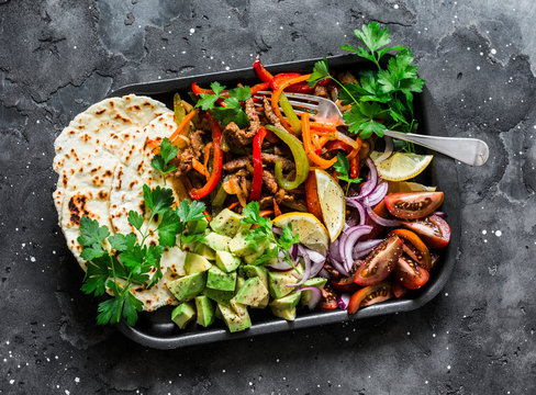 Spicy beef, vegetables, avocado, corn tortillas fajitas on a sheet pan on a dark background, top view. Delicious snack, tapas in mexican style