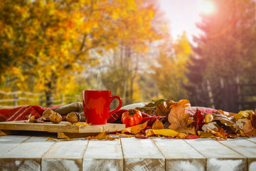 Autumn background with white wooden table board and mug on it. Blurred colourful trees view in...