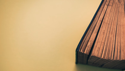 Close up Beautiful open old book top view on a yellow background table.