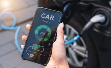 Woman Charging Electric car with Cable Looking at App On Mobile Phone. Close up of smartphone screen. Hand holding smart device. Mobile application for eco transportation.