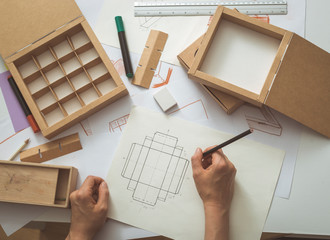 The designer develops, draws sketches for eco-packaging, cardboard boxes.