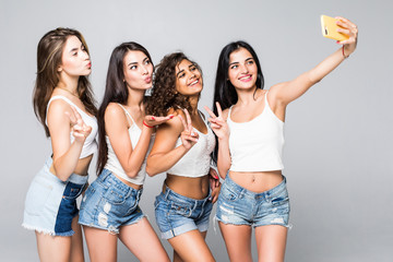 Four girlfriends make selfies isolated on white background