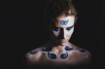 The oriental patterns on the skin of a woman, photo isolated on black background. Body art. Body painting