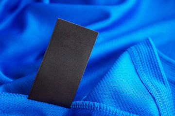 Black blank laundry care clothes label on blue jersey polyester sport shirt background Fototapete