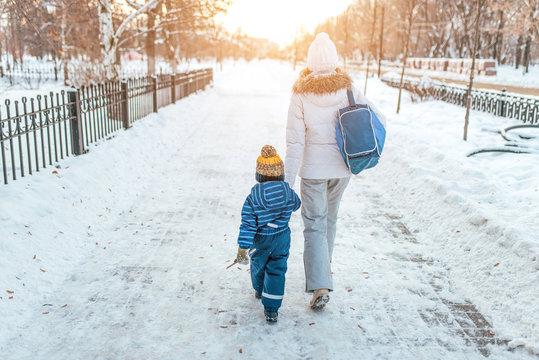 Woman mother walks down street winter, with small child, boy or girl 3-5 years old, view from rear, background road snowdrifts, returns kindergarten school workout. Holiday weekend warm clothes.