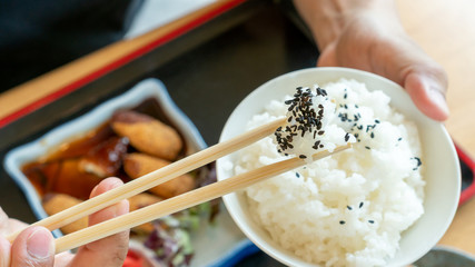 Man holding chopsticks and bowl of Japanese rice on a Japanese food background.