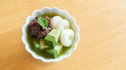 Japanese dessert (Matcha, dango, tofu, and red bean) in a bowl on a wooden table.