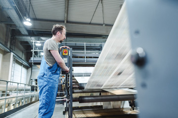 Technician on printing press monitoring the paper stream