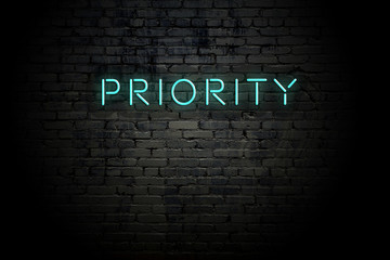 Highlighted brick wall with neon inscription priority
