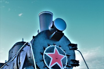 front view of an old locomotive with a red star against the sky